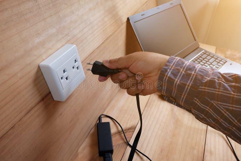 Obstrua dentro o carregador do cabo de alimentação do adaptador do laptop no assoalho de madeira imagens de stock royalty free