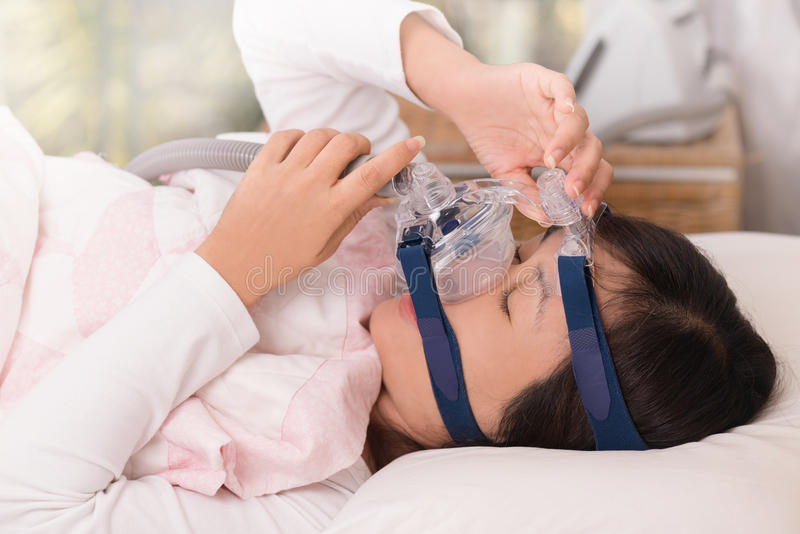 Obstructive sleep apnea therapy, Woman adjusting CPAP mask. royalty free stock images