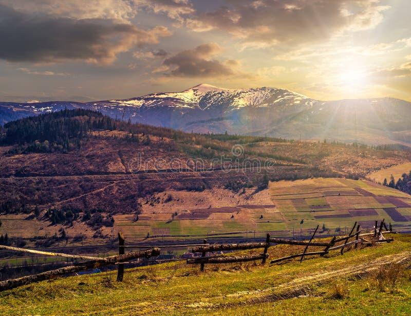 Obszar wiejski z śnieżnymi góra wierzchołkami przy zmierzchem obrazy royalty free