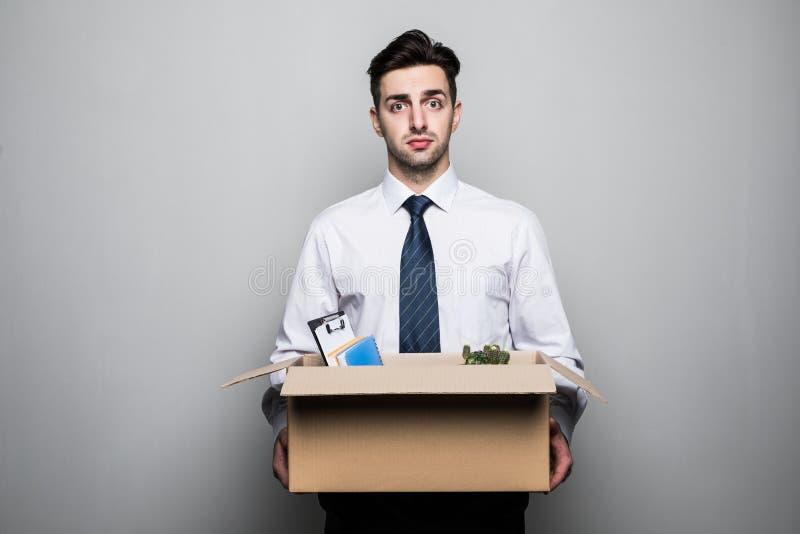 Obtenção despedido Homem de negócios novo considerável no terno no escritório com a caixa com seu material imagens de stock royalty free
