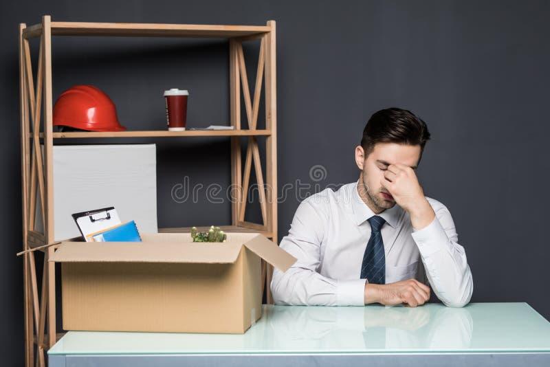 Obtenção despedido O homem de negócios considerável no terno está sentando-se tristemente na tabela no escritório perto da caixa  fotografia de stock
