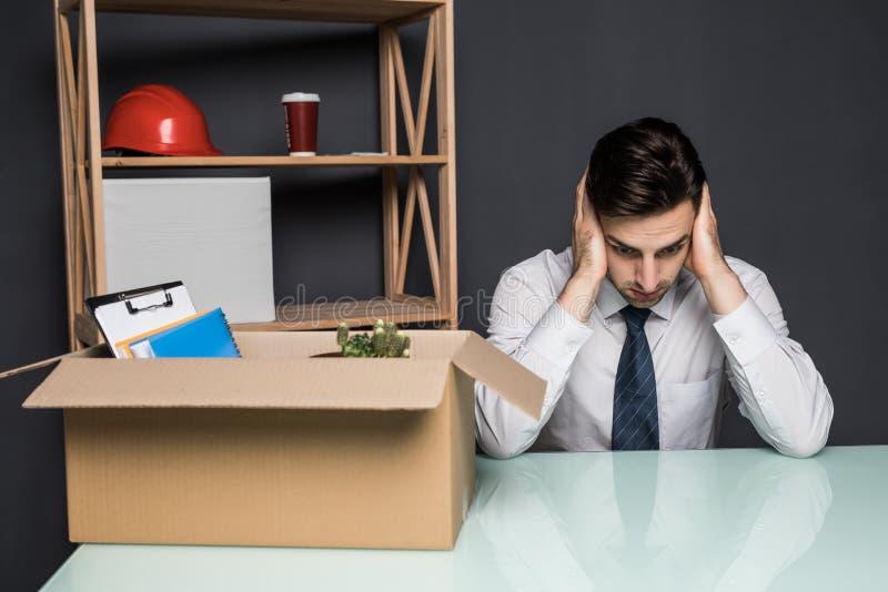 Obtenção despedido O homem de negócios considerável no terno está sentando-se tristemente na tabela no escritório perto da caixa  imagem de stock