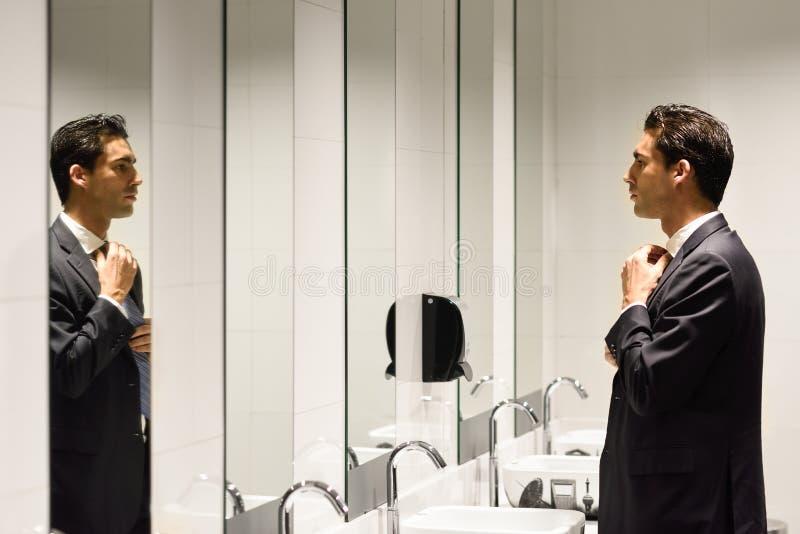 A obtenção do homem vestiu-se em um local de repouso público com espelho fotografia de stock