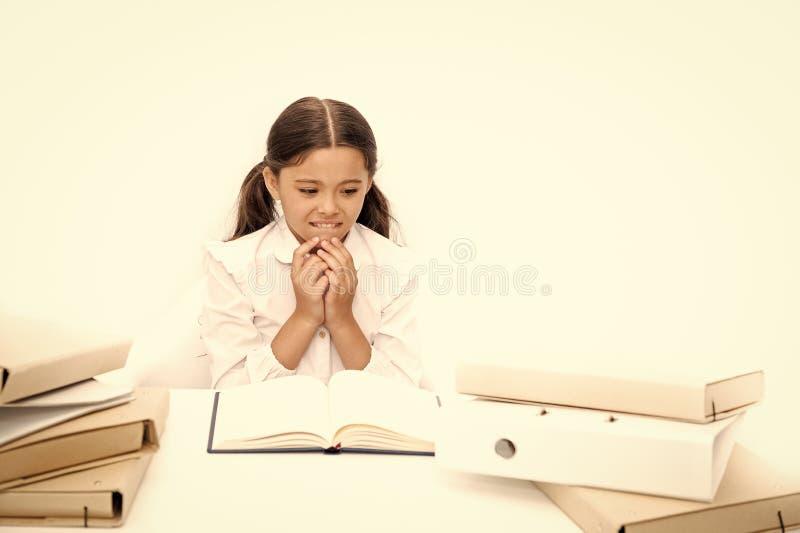 Obtendo a educa??o na leitura O aluno pequeno tem a li??o da literatura Livro de escola da leitura da estudante na mesa fotos de stock