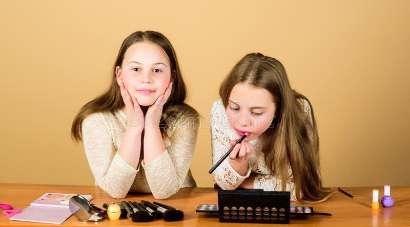 Obtenez créatif avec la collection de maquillage Peu maquilleurs au travail Petites filles mignonnes appliquant le maquillage sur image stock