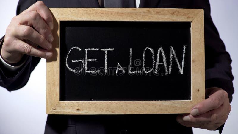 Obtenha um empréstimo escrito no quadro-negro, homem de negócios que guarda o sinal, conceito do negócio imagens de stock