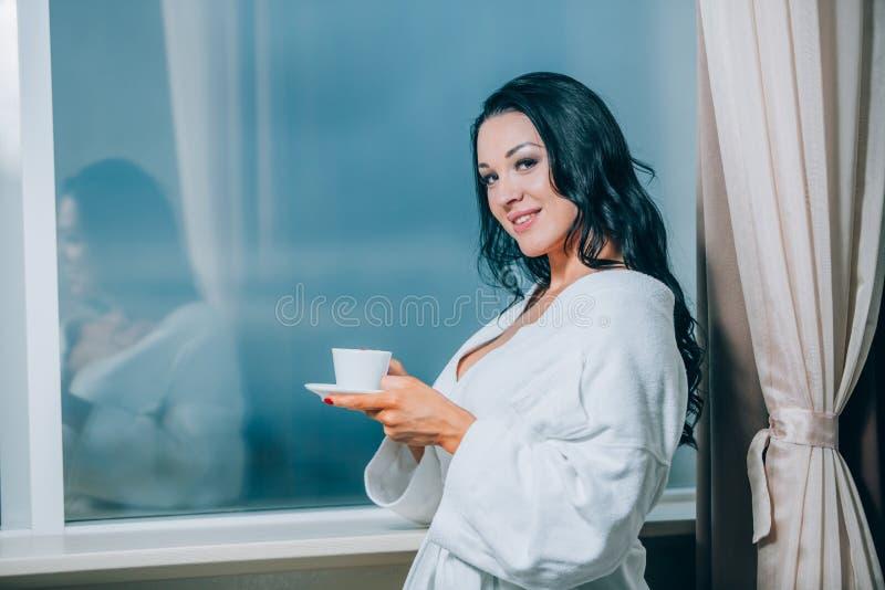 Obtention chaude avec du café frais Belle jeune femme en café potable de peignoir blanc et regard par une fenêtre photographie stock libre de droits