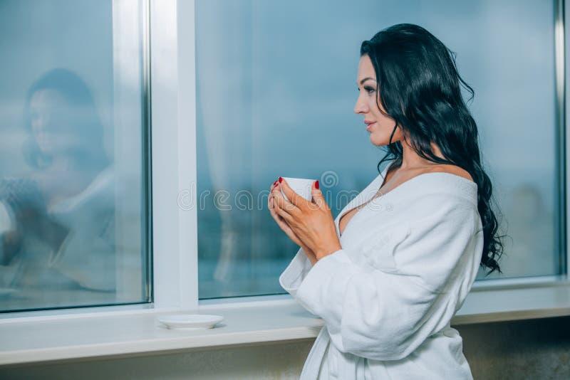 Obtention chaude avec du café frais Belle jeune femme en café potable de peignoir blanc et regard par une fenêtre image stock