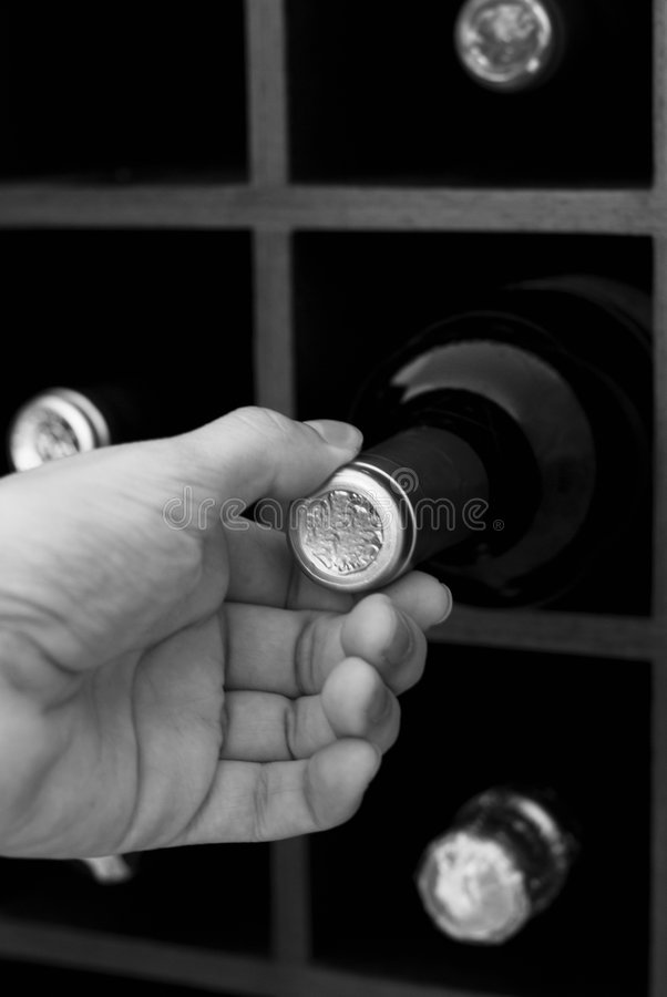 Obtention d'une bouteille de vin sur la caverne image stock