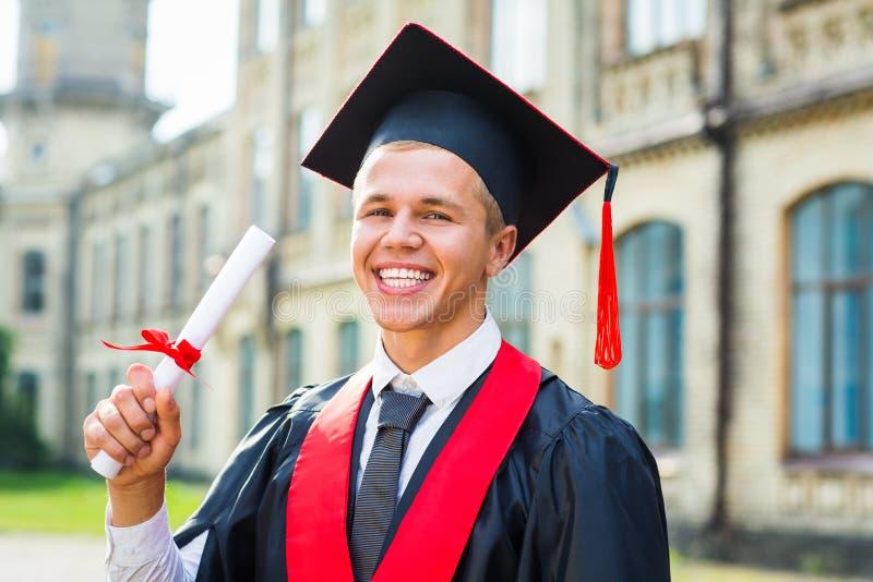 Obtention du diplôme : Étudiant Standing With Diploma photographie stock libre de droits