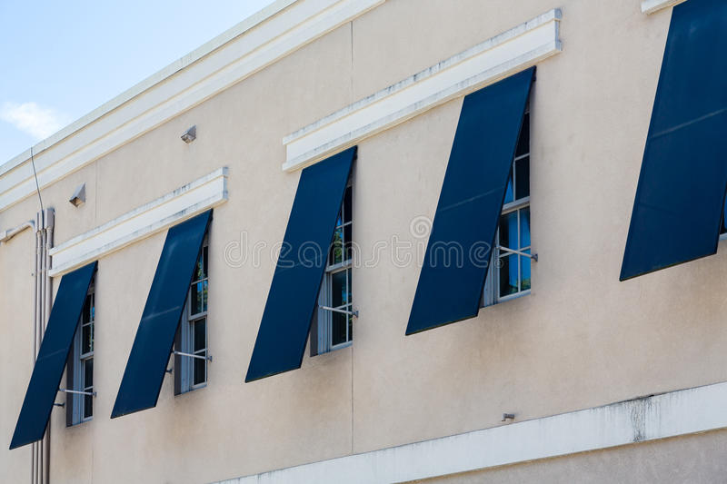 Obturadores azuis da tempestade na construção do estuque imagens de stock