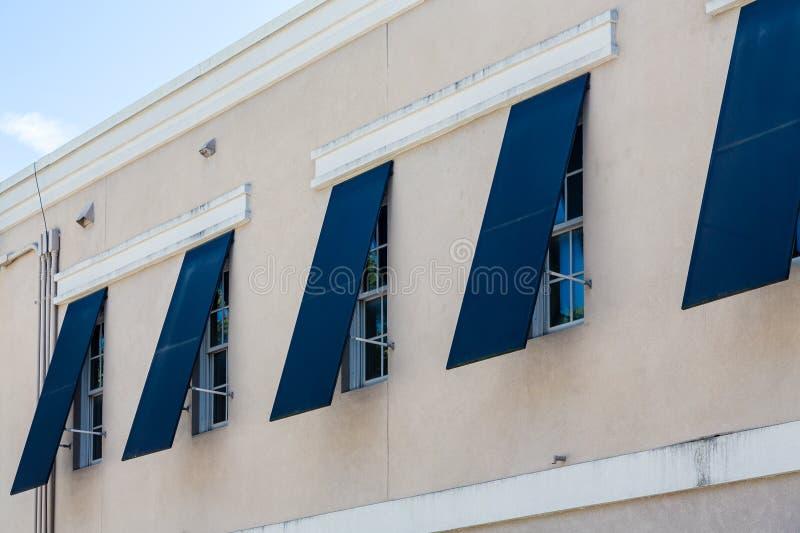 Obturadores azules de la tormenta en el edificio del estuco imagenes de archivo