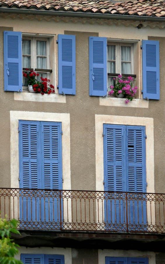 Obturadores azules del bígaro, Geranimums rosado y rojo brillante de un hogar de Provencal libre illustration