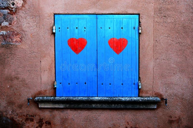 Obturadores azules viejos de la ventana con los corazones rojos imágenes de archivo libres de regalías