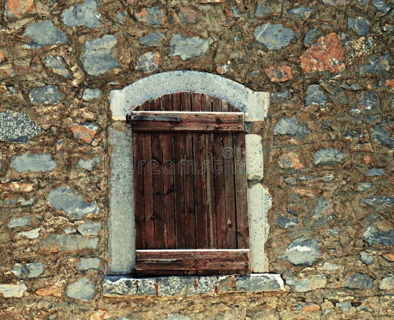 Obturadores de madeira ásperos na parede de pedra velha fotos de stock royalty free