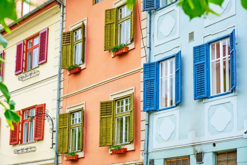 Obturadores de madera rojos, verdes, y azules coloridos en las ventanas blancas, en día brillante Tres edificios de lado a lado e fotografía de archivo