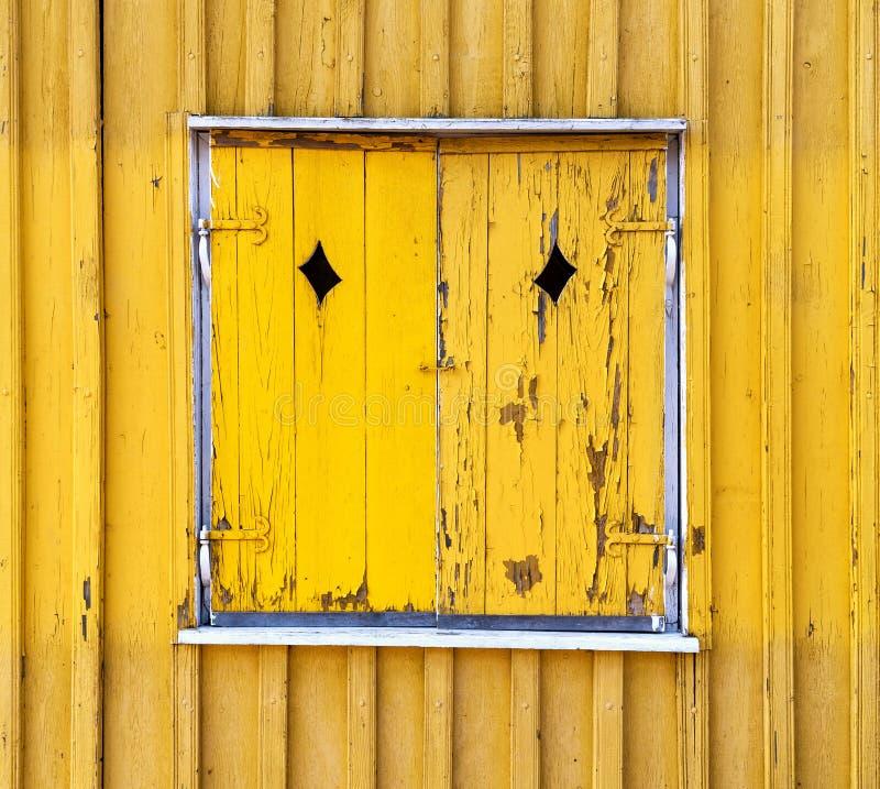 Obturadores pintados de madera amarillos de la ventana, textura del fondo fotografía de archivo