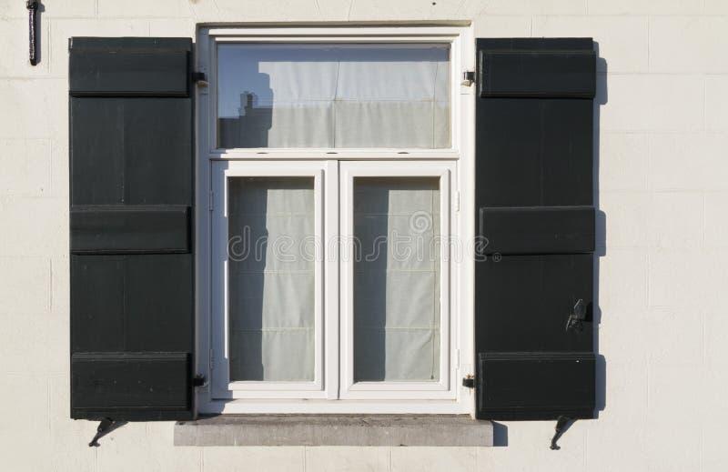 Obturadores verdes velhos ao lado das janelas e da parede de tijolos branca imagens de stock royalty free
