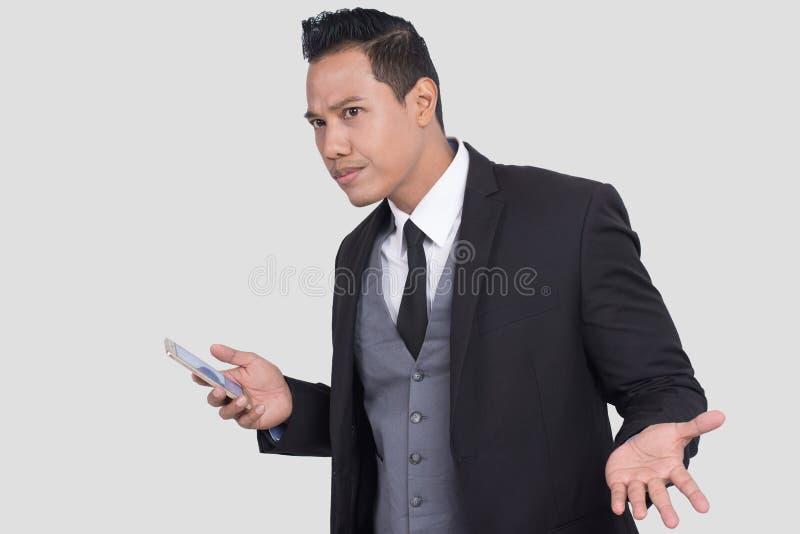 Oburzony Azjatycki biznesmen ma problem z smartphone, Nieświadomy niemy facet ma kłopoty z jego nowym mądrze telefonem zdjęcia royalty free