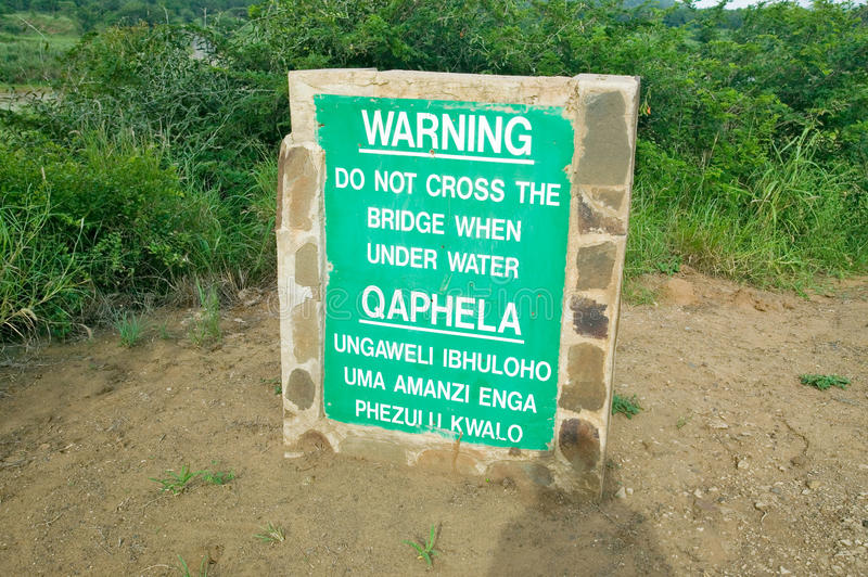 Obvious sign warns not to cross bridge when under water in Umfolozi Game Reserve, South Africa, established in 1897 stock photos