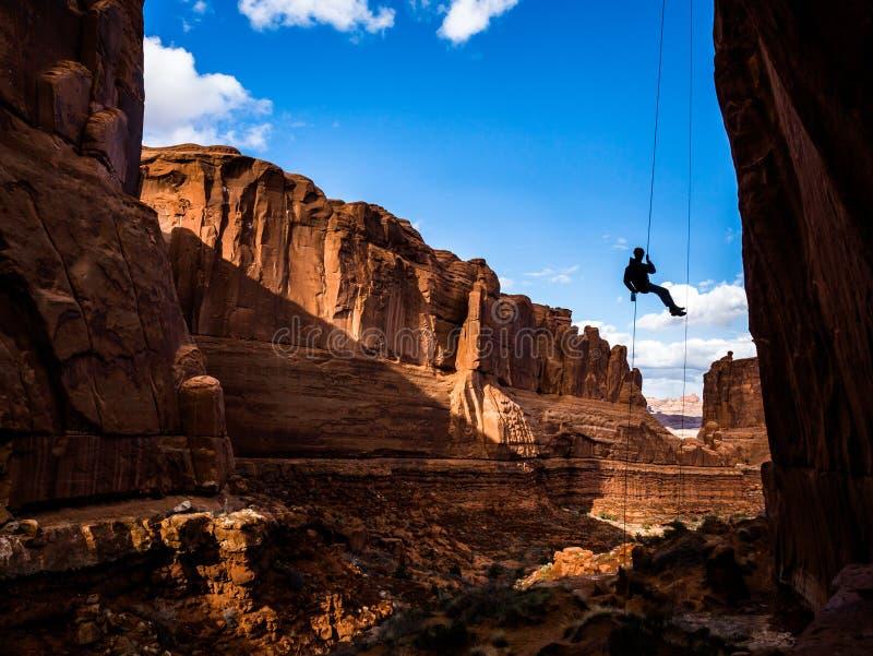 Obwieszenie Rappel w ?uku parka narodowego jar w Po?udniowej Utah pustyni obraz stock