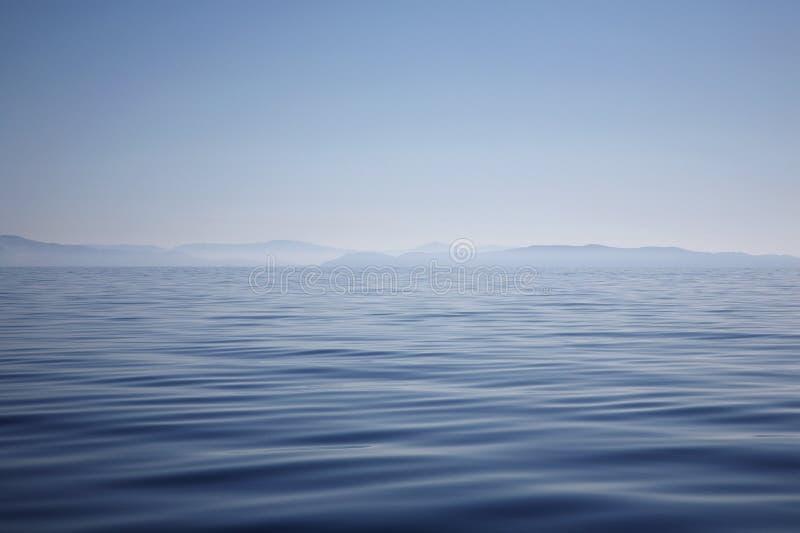 Océan avec le rivage flou de montagne photos libres de droits