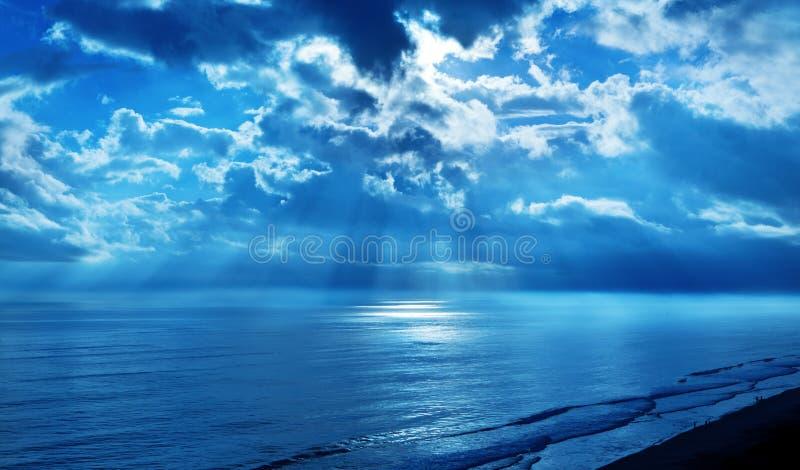 Océan de ciel bleu de nuages de rayons photo stock