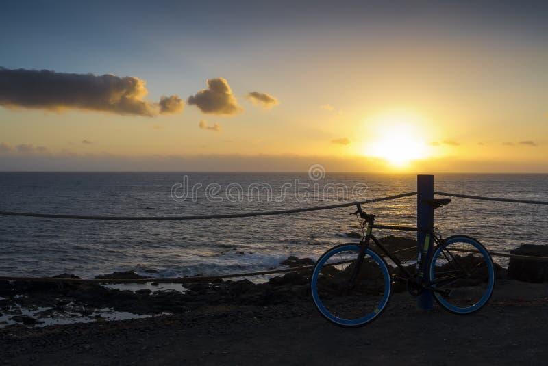 Océan de falaise de coucher du soleil de bicyclette photographie stock libre de droits