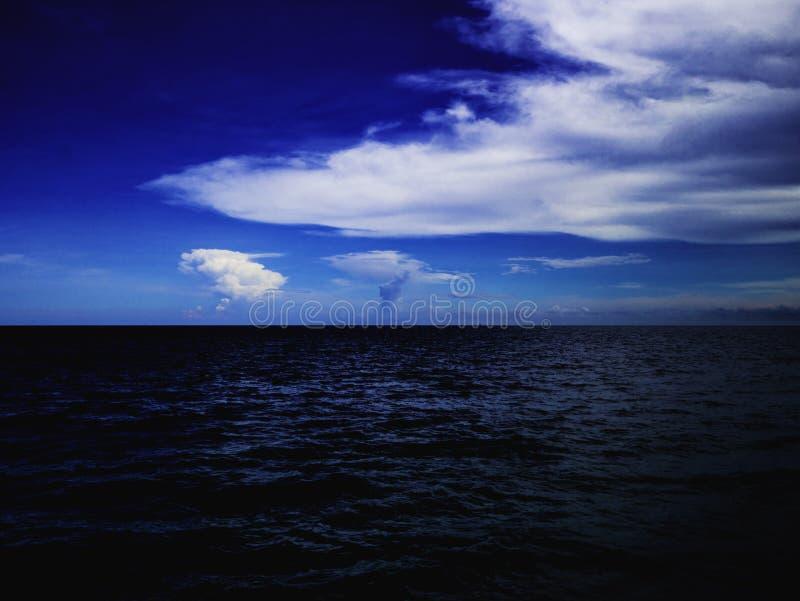 Océan idyllique étonnant et ciel nuageux avec l'horizon sans fin photos stock