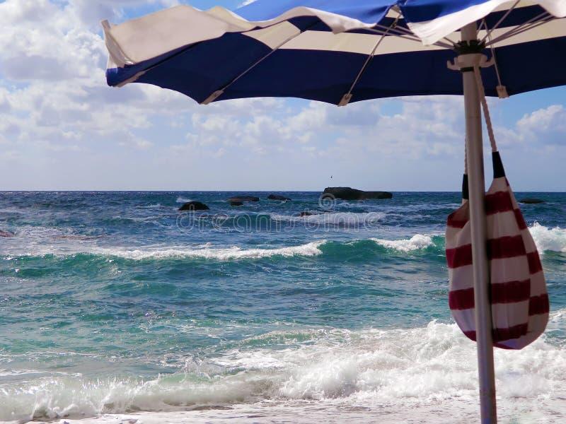 Océan orageux dans un jour ensoleillé et un parapluie de plage image stock