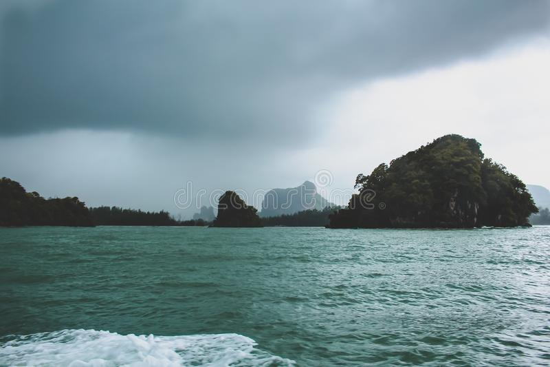 Océan tropical avec la tempête de pluie et les îles images stock