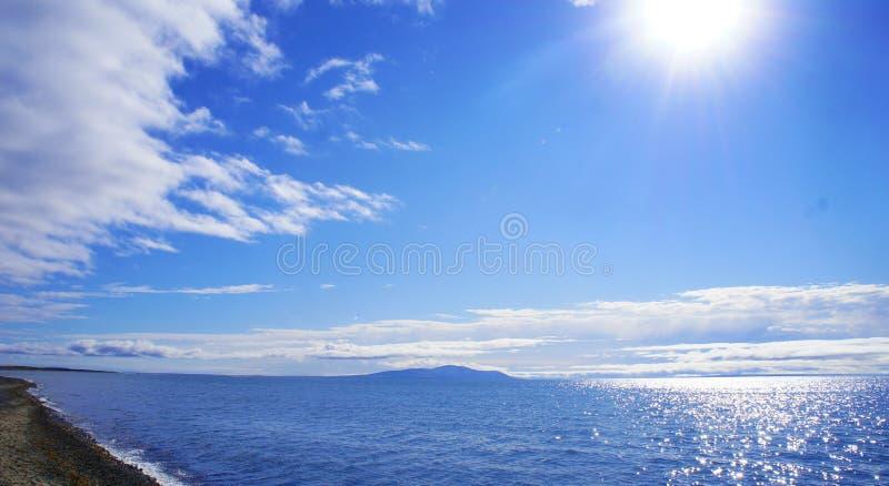 Océano azul hermoso y una pequeña isla imagen de archivo libre de regalías