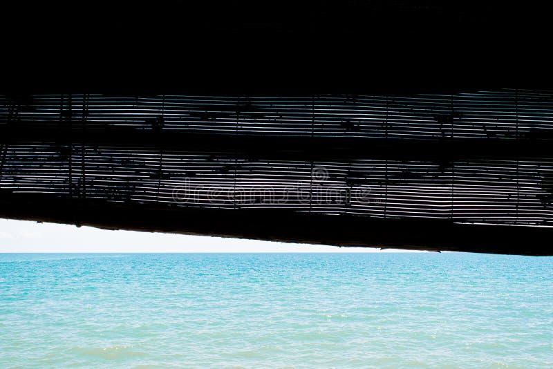 Océano del día de verano visto de persianas de madera abiertas foto de archivo libre de regalías