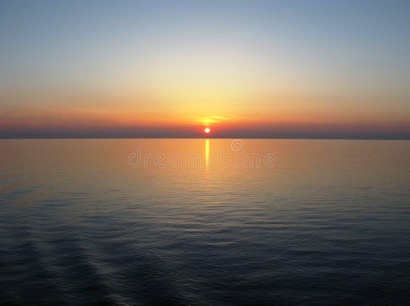 Océano Pacífico con el horizonte claro, puesta del sol, reflexión del cielo azul en el agua tranquila imagen de archivo libre de regalías