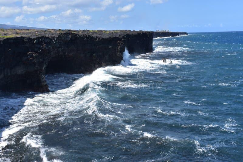 Océano Pacífico que se estrella contra los acantilados volcánicos en Hawaii imágenes de archivo libres de regalías