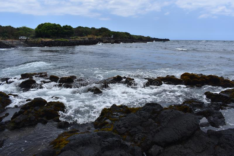 Océano Pacífico que se estrella contra los acantilados volcánicos en Hawaii foto de archivo