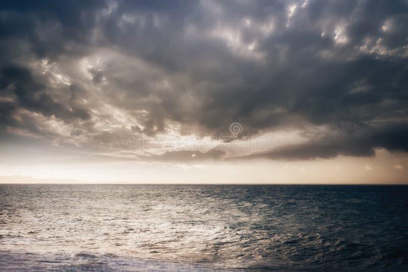 Océano tempestuoso con el cielo nublado de la puesta del sol imágenes de archivo libres de regalías