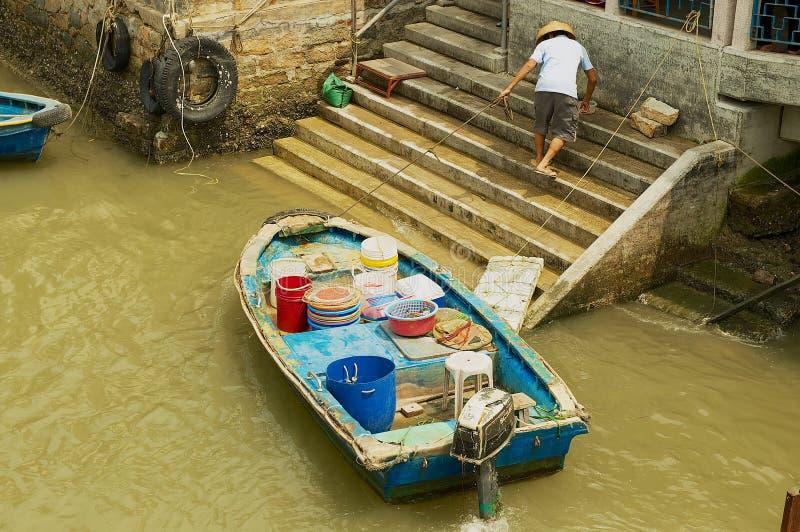 Ocal渔夫在大澳渔夫村庄栓一条老小船在香港,中国 免版税库存照片