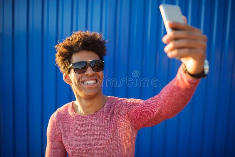 Ocasional feliz novo do homem vestido com fones de ouvido e o telefone esperto no fundo amarelo fotografia de stock royalty free