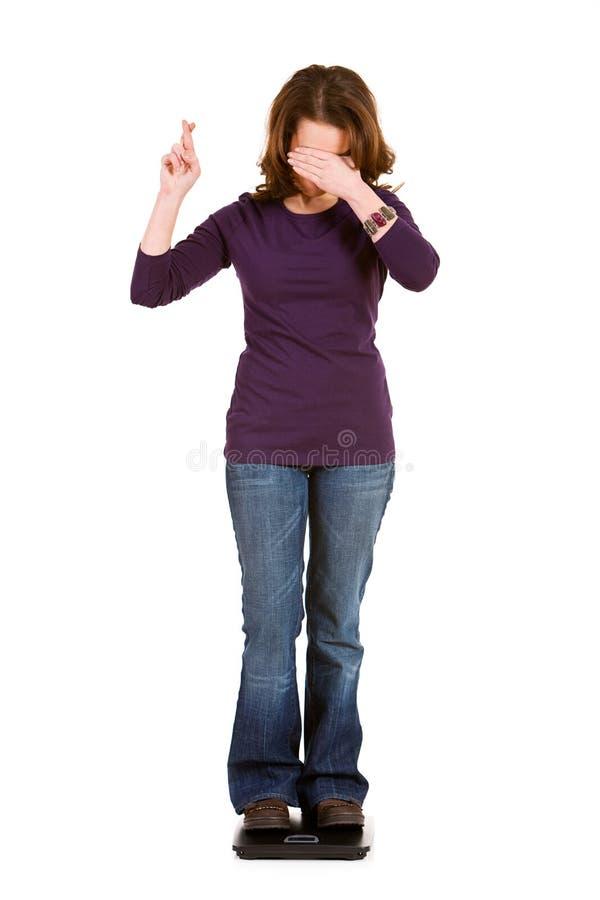 Ocasional: Mulher com espera cruzada dedos para a perda de peso fotos de stock