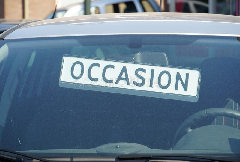 Occasion car for sale. The word Occasion behind the windshield of a car outside a garage, indicating the car is for sale royalty free stock photos
