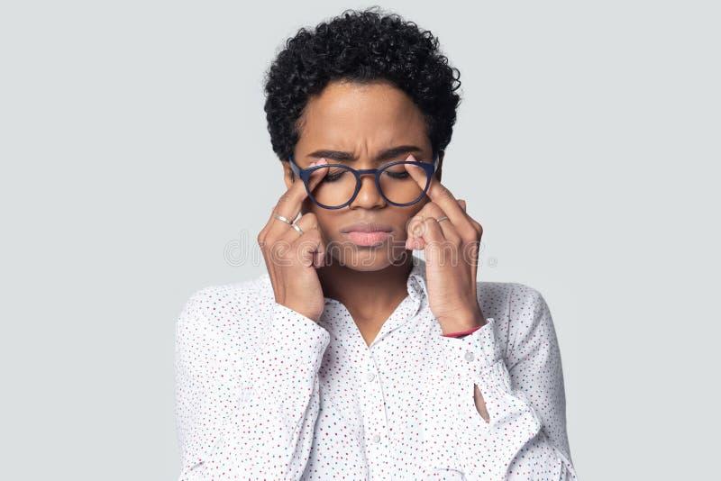 Occhi afroamericani esauriti di massaggio della donna che soffrono dall'emicrania fotografia stock libera da diritti