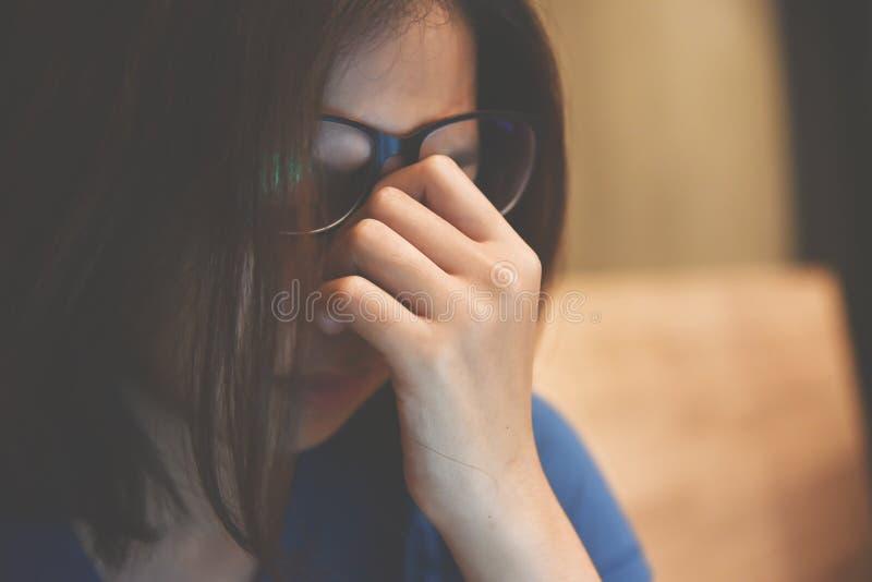 Occhi asiatici stanchi dello sfregamento della donna degli occhiali immagini stock