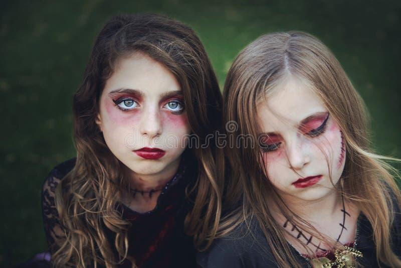Occhi azzurri delle ragazze del bambino di trucco di Halloween in prato inglese all'aperto fotografie stock