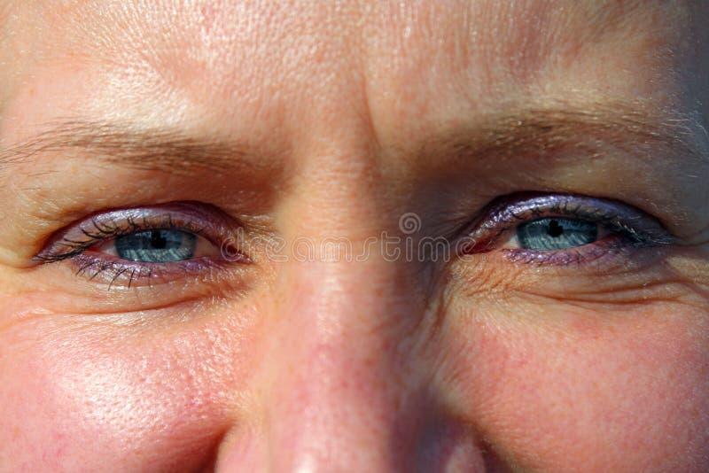 Occhi azzurri femminili Fronte della fine attraente della donna su immagine stock libera da diritti
