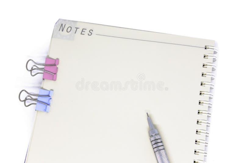 Occhi e penna neri di vetro sul taccuino bianco immagine stock