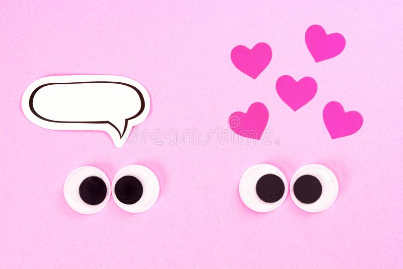 Occhi Googly Coppie sconosciute gli amanti strabici su fondo rosa con alcuni piccoli cuori e sullo spazio della copia per i pensi immagini stock