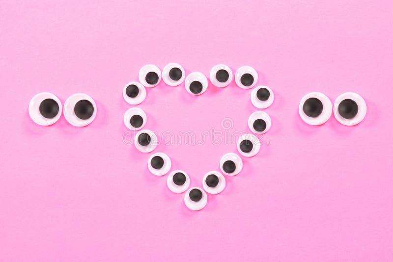 Occhi Googly Occhi sconosciuti delle coppie gli amanti su fondo rosa Con un segno del cuore nel fratempo immagine stock libera da diritti