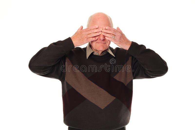 Occhi maggiori della copertura dell'uomo più anziano fotografia stock