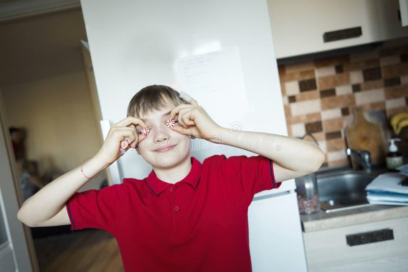Occhi vicini del ragazzo divertente con la caramella come i vetri immagine stock